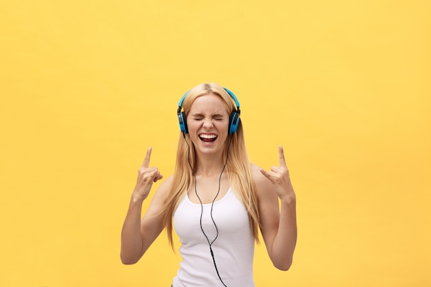 Lifestyle portrait of a happy woman listening music in headphones isolated on a yellow background