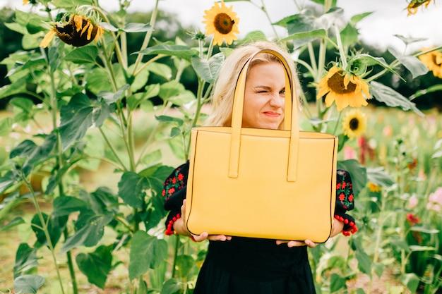 Портрет образа жизни od необычная нечетная красивая белокурая девочка в черной вышивке с украшением, держащим желтую кожаную сумку в цветочном саду. странная странная женщина с эмоциональным смешным лицом, одетая в очаровательное платье