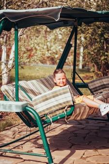 정원 그네에 앉아 드레스를 입은 귀여운 6세 소녀의 라이프스타일 초상화