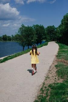 Образ жизни портрет обезличенной девушки, едущей на скутере по реке в парке на семейном ...