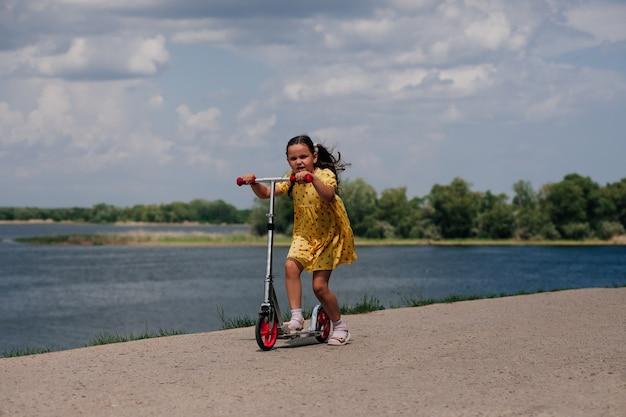 川岸に沿って高速でスクーターに乗っている女の子のライフスタイルの肖像画スクーターを持った女の子...