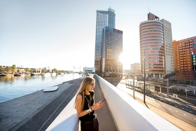 アムステルダム市の朝の背景に高層ビルとモダンな橋の上に電話で立っているスタイリッシュな女性のライフスタイルの肖像画