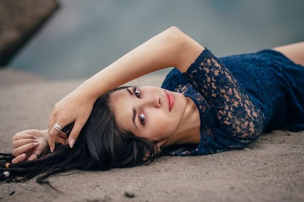 흐린 날에 모래에 누워 호수의 배경에 여자 갈색 머리의 라이프 스타일 초상화. 낭만적이고 부드럽고 신비로운