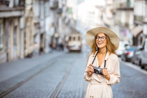 ポルトガル、ポルト市の背景に有名な古い観光トラムと通りに立っている女性旅行者のライフスタイルの肖像画