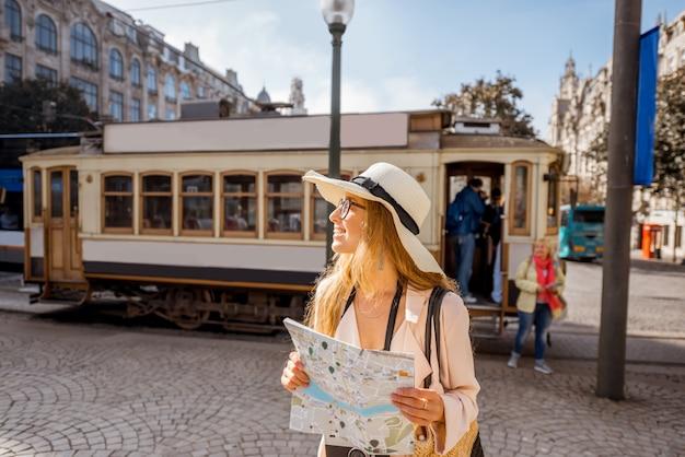 ポルトガルのポルト市の通りにある有名な古い観光トラムの近くに紙の地図を持つ女性のライフスタイルの肖像画