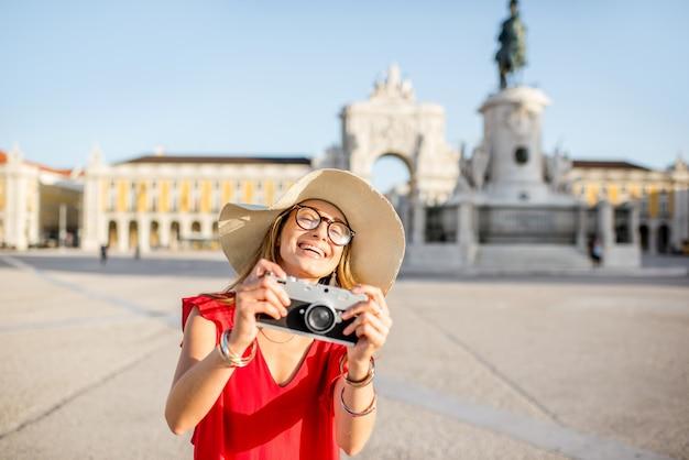 ポルトガル、リスボン市の朝の光の中で像と凱旋門を背景にメイン広場に立っている若い女性の観光客のライフスタイルの肖像画