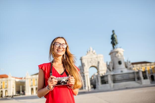 Образ жизни портрет молодой женщины-туриста, стоящего на главной площади со статуей и триумфальной аркой на заднем плане во время утреннего света в городе лиссабон, португалия