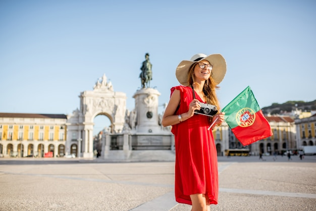 Образ жизни портрет молодой женщины-туриста с португальским флагом, стоящей на главной площади в утреннем свете в городе лиссабон, португалия