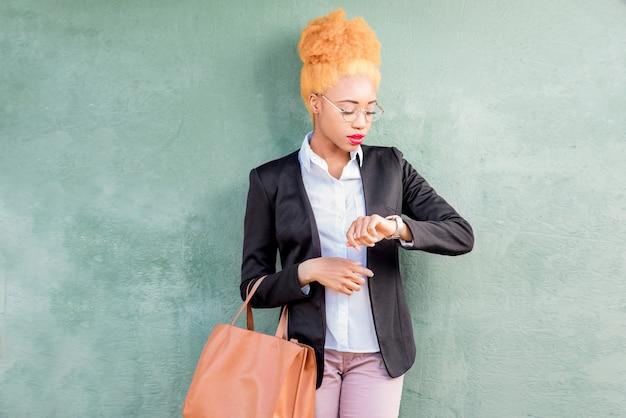 緑の壁の背景にバッグを保持しているカジュアルなスーツを着たアフリカの実業家のライフスタイルの肖像画