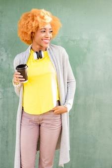 緑の壁の背景にコーヒーと立っているカジュアルな服を着たアフリカの女性のライフスタイルの肖像画
