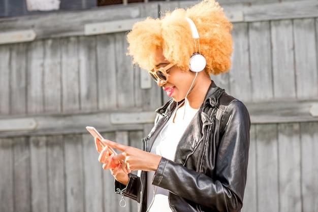 木製の壁の背景に立っているスマートフォンで音楽を聴いている革のジャケットのアフリカの女性のライフスタイルの肖像画