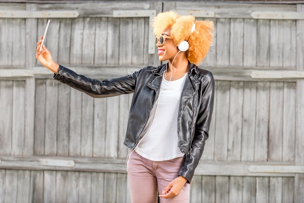 나무 벽 배경에 전화기가 서 있는 셀카 사진을 만드는 가죽 재킷을 입은 아프리카 여성의 라이프스타일 초상화