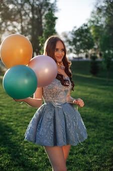 Образ жизни портрет привлекательной сексуальной женщины в коротком синем вышитом платье с разноцветными шариками ...