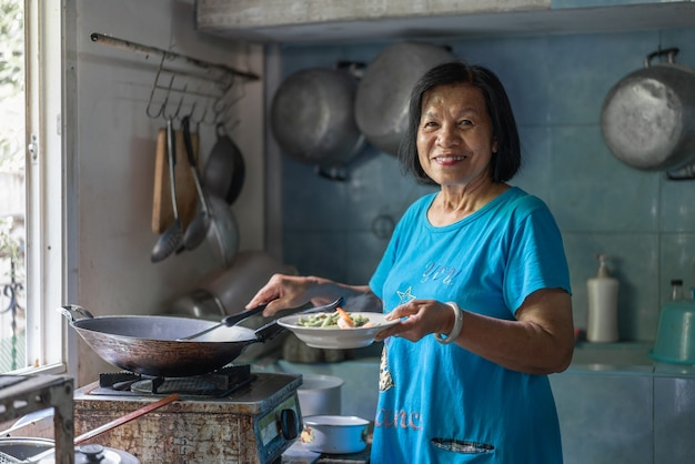 Портрет образа жизни азиатской пожилой женщины, улыбающейся и счастливой, готовящей тайскую еду на кухне дома