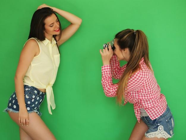 写真カメラと一緒に立っている美しい親友の流行に敏感な女の子のライフ スタイルの肖像画は、1 つの写真を撮りながら楽しい時を過します。緑の壁越し。