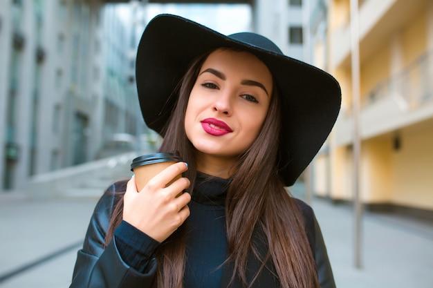 Портрет образа жизни красивой модели брюнетки с чашкой кофе, носящей широкополую шляпу. кофе с собой концепция