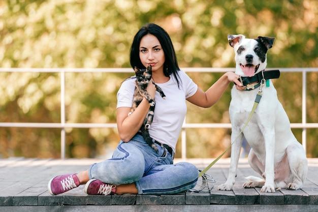 小さな猫と公園に屋外に座っている大きな犬と美しいブルネットの女性のライフスタイルの肖像画。