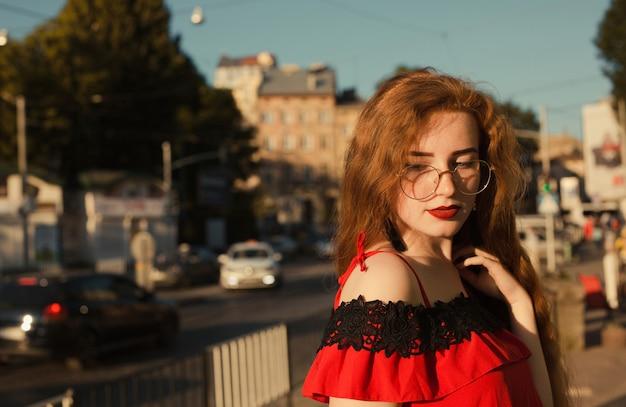 そばかすのある美しい赤毛の女の子のライフスタイルの肖像画。眼鏡をかけた長い巻き毛のモデル。 。テキスト用のスペース