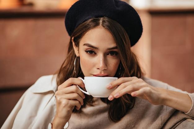어두운 물결 모양의 헤어스타일, 트렌디한 메이크업, 세련된 베이지색 풀오버와 코트, 카페 테라스에 앉아 흰색 컵으로 커피를 마시는 우아한 젊은 여성의 라이프스타일 초상화