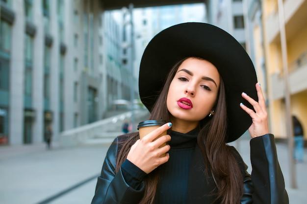 Портрет образа жизни модной модели брюнетки с чашкой кофе, носящей широкополую шляпу. кофе с собой концепция