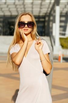 회색 재킷을 들고 도시를 걷고 있는 트렌디한 드레스를 입은 매력적인 금발 소녀의 라이프스타일 초상화