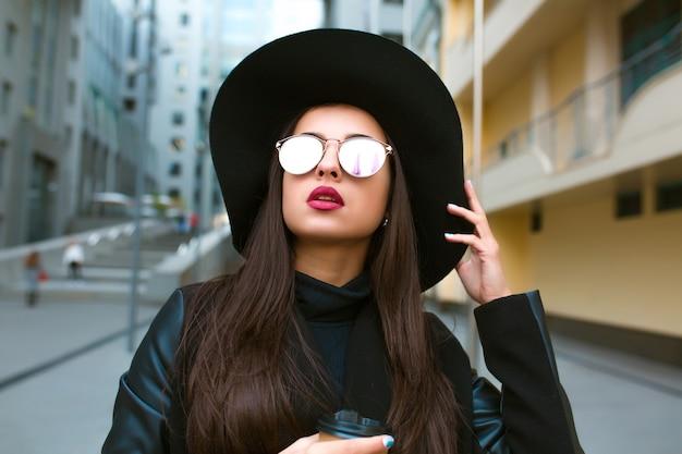 Портрет образа жизни гламурной молодой модели с чашкой кофе в широкополой шляпе и очках. кофе с собой концепция