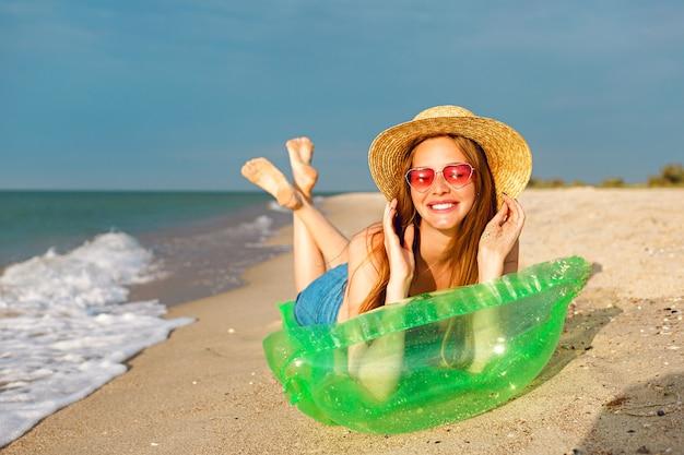 幸せな美しさのブロンドの女性のライフスタイルの肖像画は、ビーチで日光浴をし、笑顔で夏休みを楽しむエアマットレスに横たわっていた