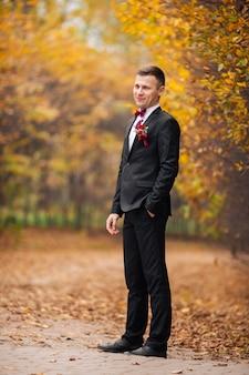 背景のオークの木と自然に屋外カメラにポーズをとって幸せな新郎のライフスタイルの肖像画。ジャクセット、ボウタイ、白いシャツの肖像画で顔を笑顔で陽気な婚約者