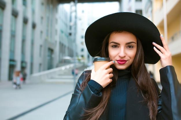 Портрет образа жизни роскошной молодой модели с чашкой кофе в широкополой шляпе. кофе с собой концепция