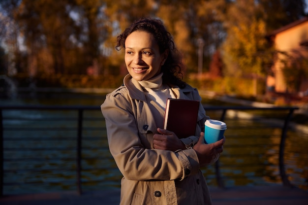 따뜻한 베이지색 코트를 입은 예쁜 여성의 라이프스타일 초상화는 테이크아웃 커피 한 잔을 들고 하드커버에 책을 껴안고 가을 공원과 호수 배경에서 웃고 있습니다. 여가 활동, 행복한 주말