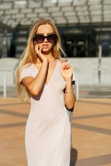 회색 재킷을 들고 도시를 걷고 있는 트렌디한 드레스를 입은 매혹적인 금발 소녀의 라이프스타일 초상화