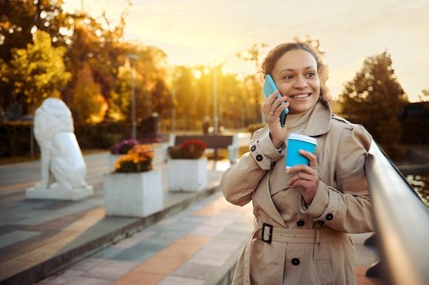 베이지색 트렌치 코트를 입은 미소 짓는 아름다운 여성이 뜨거운 음료와 함께 종이 테이크아웃 머그를 들고 도시 공원 야외에서 아름다운 가을날을 즐기는 휴대전화로 이야기하는 라이프스타일 초상화