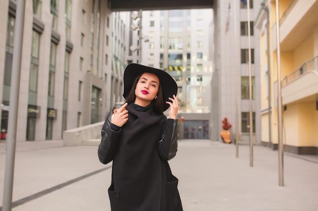 Образ жизни портрет стильной молодой модели с чашкой кофе в широкополой шляпе. кофе с собой концепция