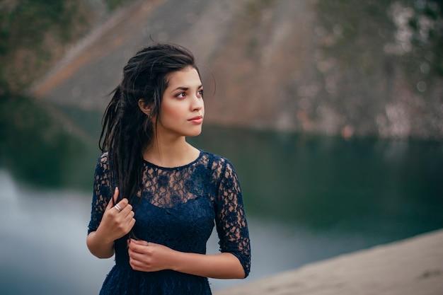 흐린 날에 모래에 호수의 배경에 여자 갈색 머리의 라이프 스타일 초상화
