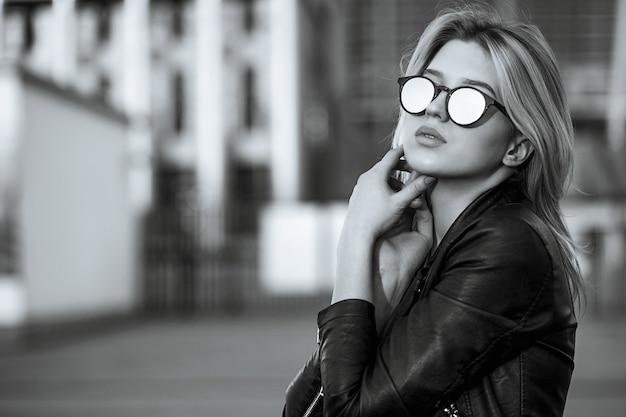ミラーサングラスと革のジャケットを着ている若いかわいい女の子のライフスタイルの肖像画。テキスト用のスペース。モノクロ調色