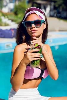 Lifestyle portrait of tanned beautiful woman in pink bikini and sunglasses sitting near swimming pool with fresh cocktail.