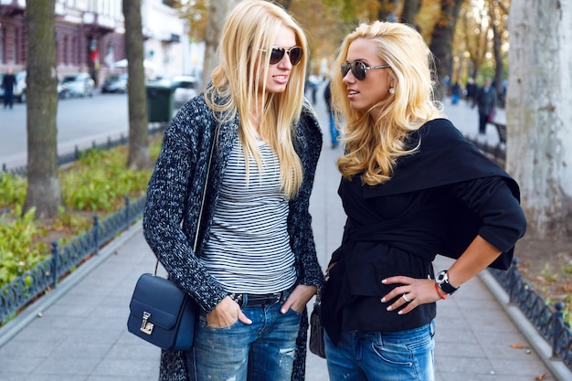 Lifestyle portrait of two best friends blonde girls spending time in the center of the city at nice fall autumn day, using smartphone, wearing sunglasses ant trendy fashion looks.