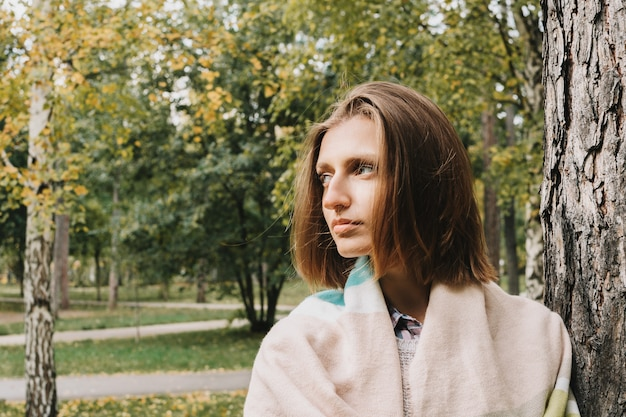 Lifestyle portrait of young adult woman wrapped in scarf in forest or park