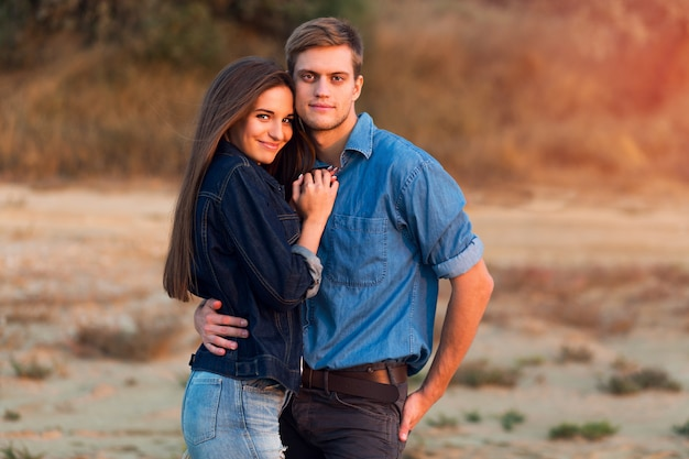 Lifestyle portrait of young attractive couple in love posing outdoor in the evening .