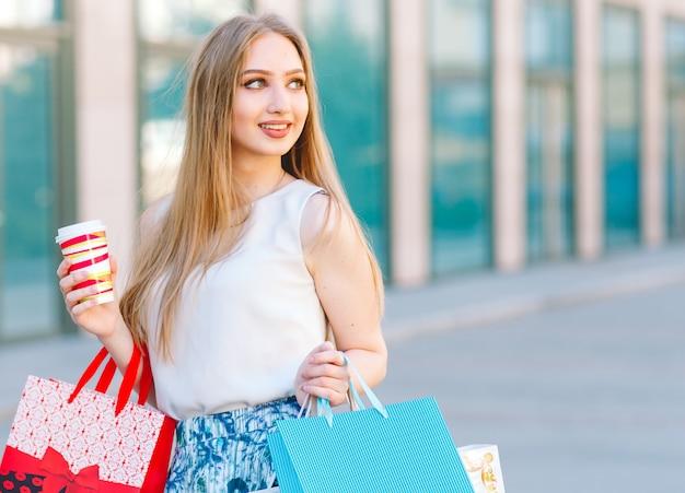 쇼핑 가방가 게에서 밖으로 걷는 라이프 스타일 초상화 젊은 금발 소녀.