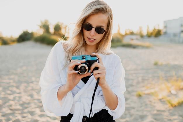 空のビーチで楽しんで写真を作るスタイリッシュなブロンドの女の子のライフスタイルのポジティブなイメージ。休日と休暇の時間。田舎の自由と自然。