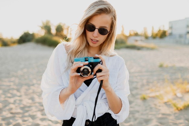Lifestyle positive image of stylish blond girl having fun and making photos on empty beach. holidays and vacation time. freedom and nature in countryside.