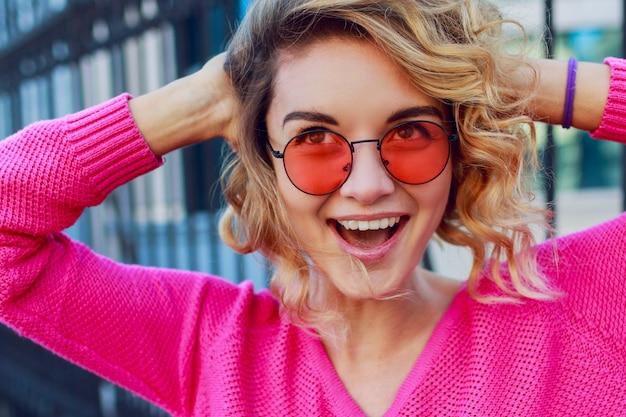 ピンクのプルオーバーで陽気な幸せな女のライフスタイルの肯定的な肖像画