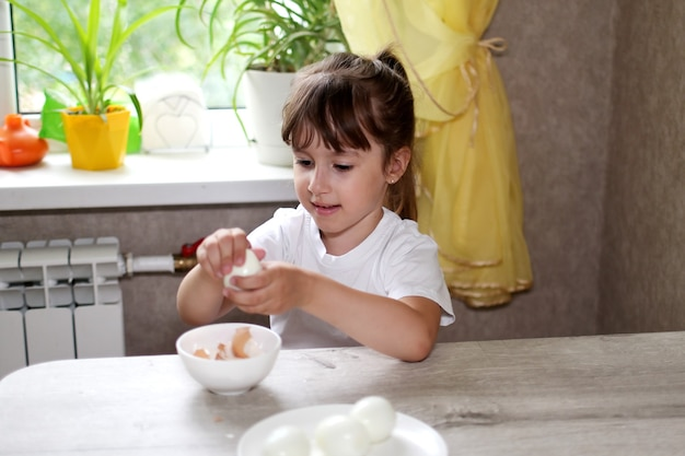 Образ жизни дошкольника ребенок девочка готовит еду на кухне. развитие мелкой моторики в повседневной жизни из подручных материалов. ребенок чистит яйца.