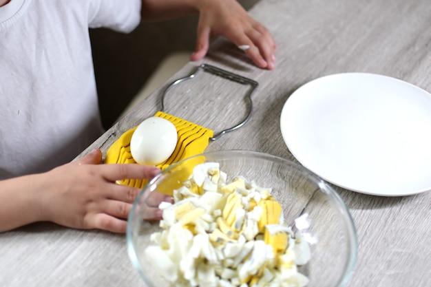 Образ жизни дошкольника ребенок девочка готовит еду на кухне. развитие мелкой моторики в повседневной жизни из подручных материалов. ребенок режет яйца желтой ножницей для яиц.