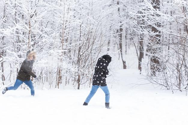 생활 방식, 계절 및 레저 개념 - 겨울 공원에서 재미있는 커플이 눈덩이를 하고 있습니다.