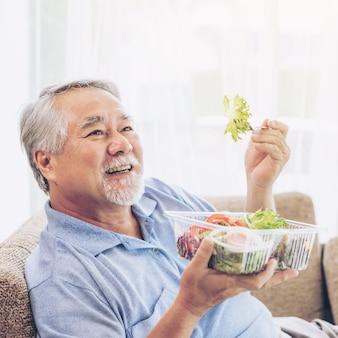 ライフスタイルの年配の男性は、自宅のソファで健康のためにダイエット食品の新鮮なサラダを食べて幸せを感じます