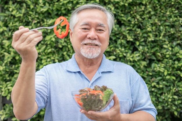 Lifestyle senior man feel happy enjoy eating diet food fresh salad on green plant nature background