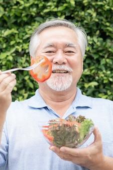 라이프스타일 노인은 녹색 식물 배경에서 다이어트 음식 신선한 샐러드 야채를 먹는 것을 즐깁니다.