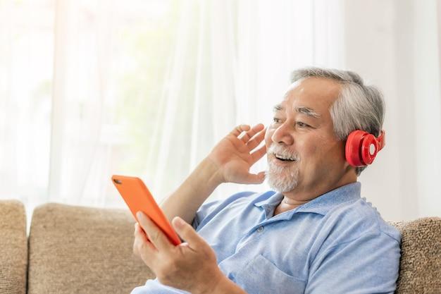 Образ жизни старший мужчина чувствует себя счастливым, наслаждаясь прослушиванием музыки в наушниках на диване у себя дома - копия пространства